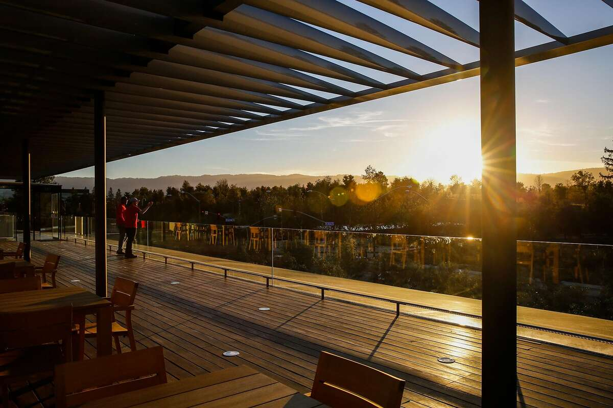 In this file photo - Apple employees (who declined to provide names) look out at the view during sunset at the Apple visitors center in Cupertino, Calif., on Monday, Nov. 27, 2017.