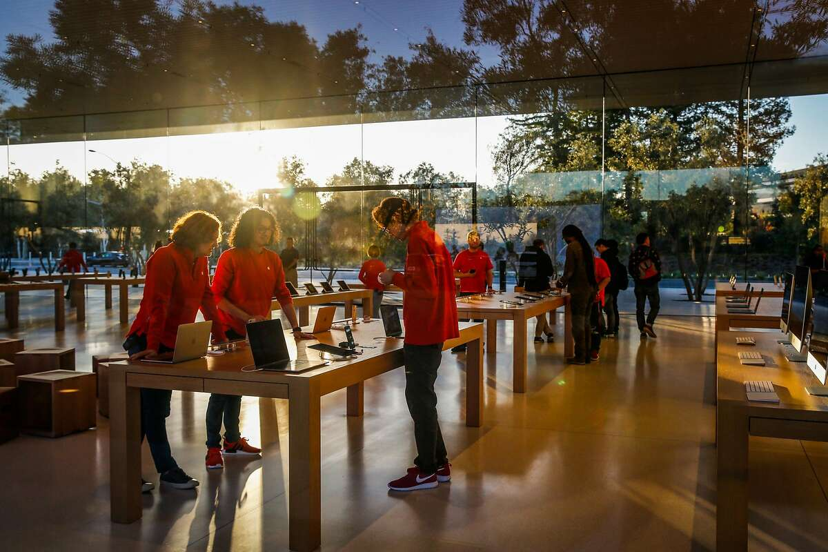Apple employees (declined names) chat as they work at the Apple visitors center in Cupertino, Calif., on Monday, Nov. 27, 2017.
