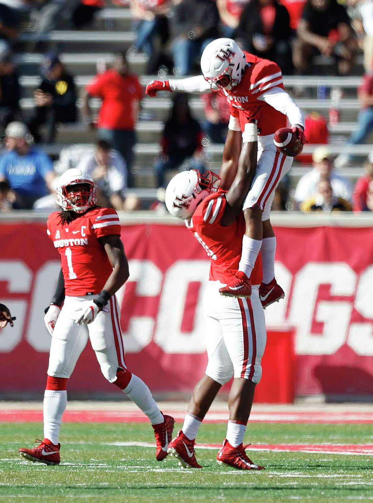 Houston Cougars cornerback Alexander Myres (18) gets lifted up by defensive end Nick Thurman (91) after Myres intercepted a pass intended for Navy Midshipmen running back Darryl Bonner in the second half of a college football game at TDECU Stadium, Friday, Nov. 24, 2017, in Houston. ( Karen Warren / Houston Chronicle )