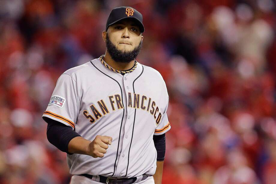 Yusmeiro Petit pumps his fist after pitching a scoreless 15th inning in Game 2 of the 2014 Division Series at Washington. He threw six shutout innings in a 2-1 Giants victory. Photo: Patrick Semansky, Associated Press