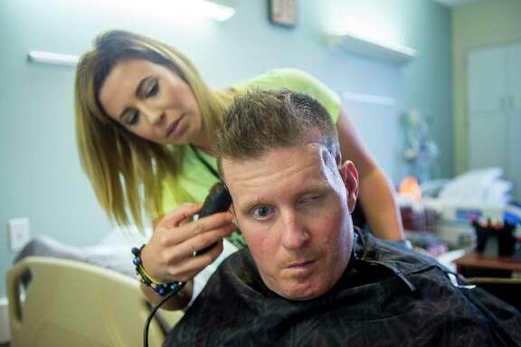 Danielle McNicoll trims fiancé Nick Tullier's hair in his room at TIRR Memorial Hermann.
