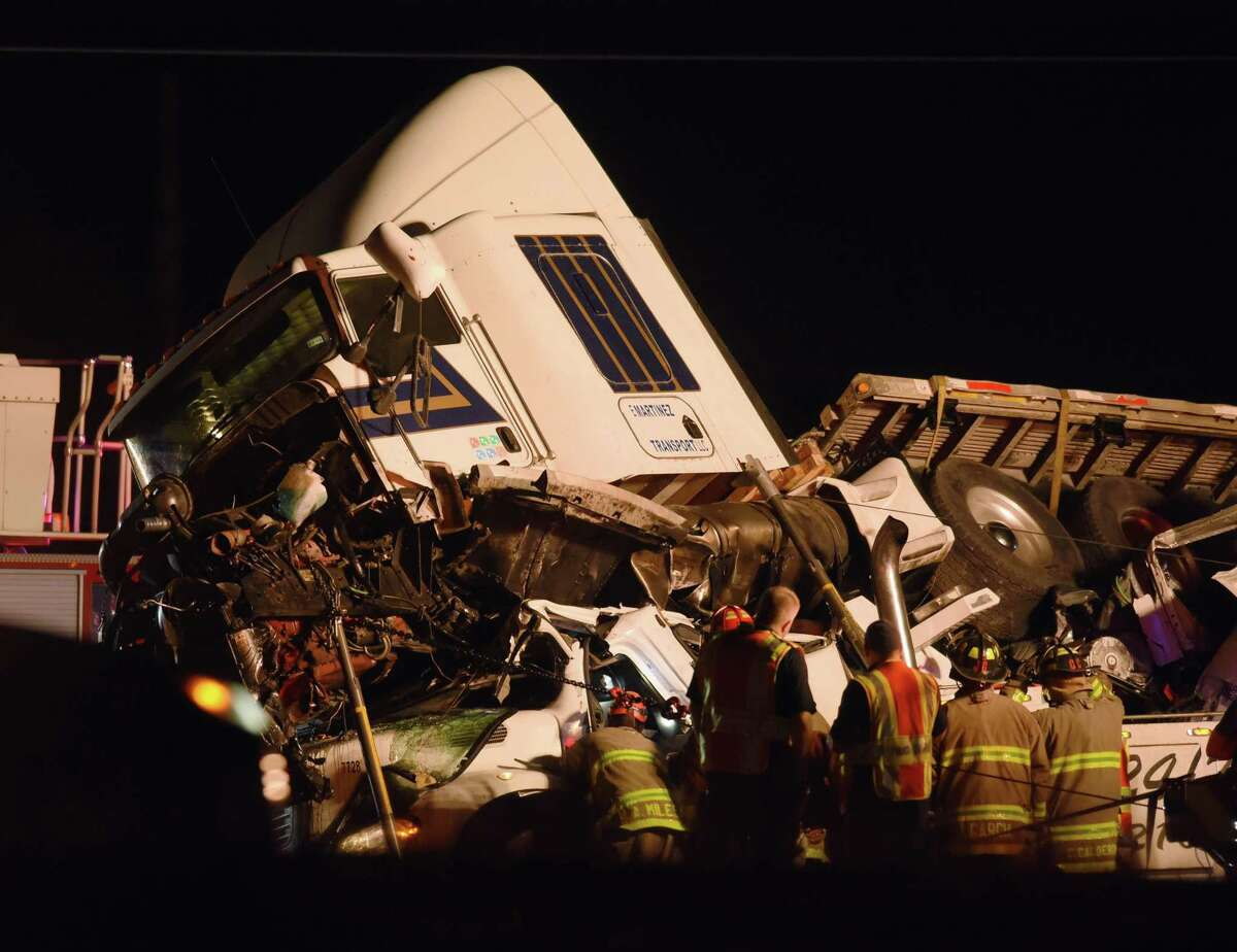 A tractor trailer rests atop a vehicle on Interstate 35 South at Somerset Road on San Antonio on Wednesday, Nov. 29, 2017. One person is known dead in the accident.