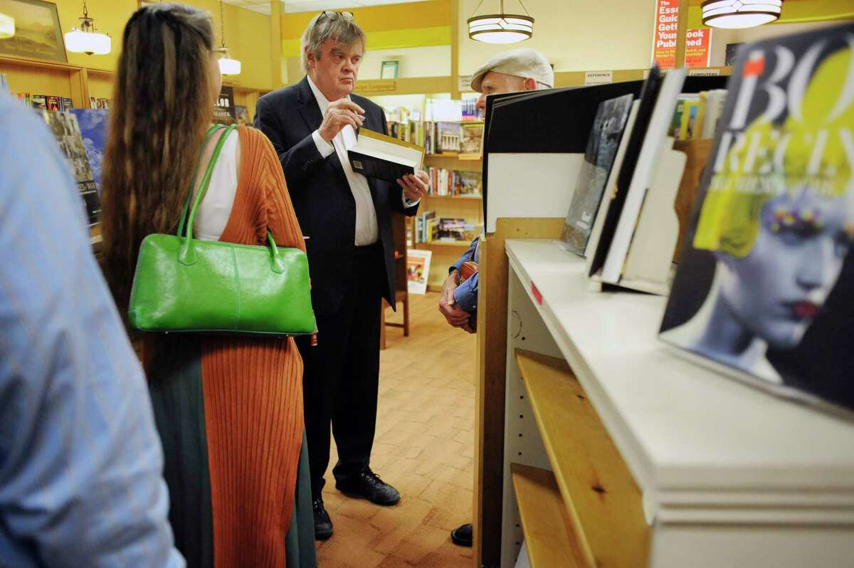 """Garrison Keillor, center, author and host of """"A Prairie Home Companion,"""" talks with a fan during a book signing at the Book House of Stuyvesant Plaza on Tuesday, May 20, 2014, in Albany, N.Y. (Paul Buckowski / Times Union)"""