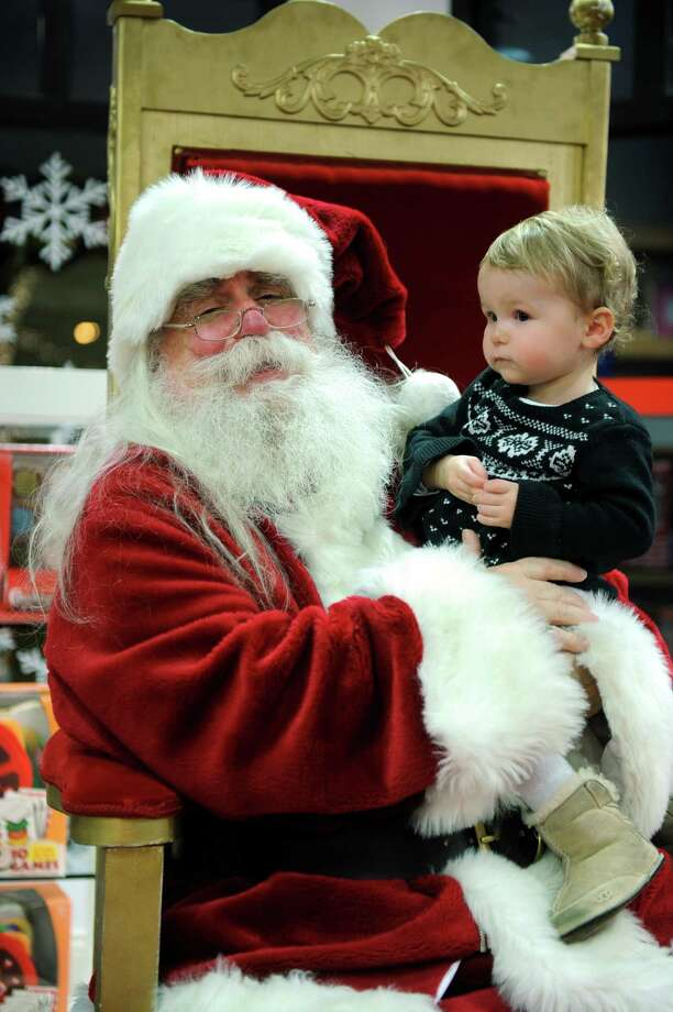 Santa Claus, aka Joe Warren, holds eighteen-month-old Avery Kollar, of Boston, MA, on December 22, 2011 at the Darien Sports Shop. Warren has been appearing at the shop in Darien, free of charge, nearly 40 years. Photo: Autumn Driscoll / Autumn Driscoll / Connecticut Post