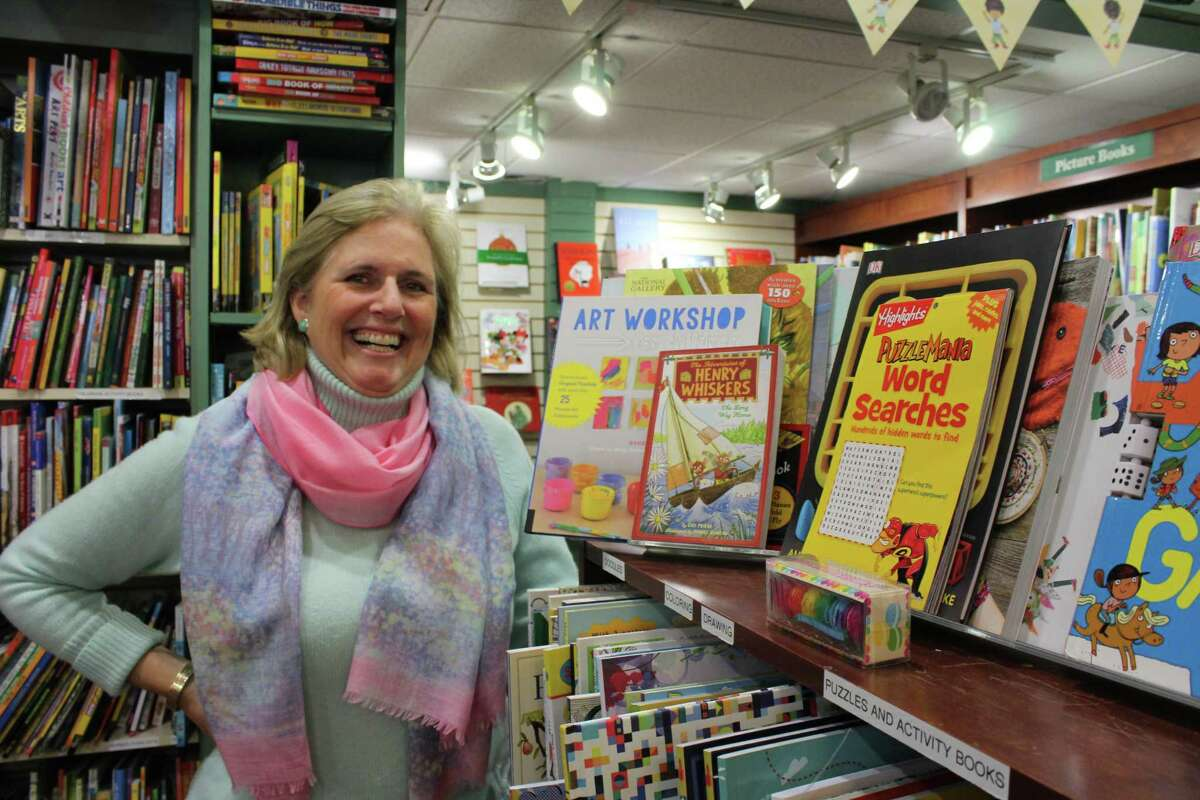 Melissa Thorkilsen, the manager of children's books at Elm Street Books in downtown New Canaan, stands next to some books written by local authors.