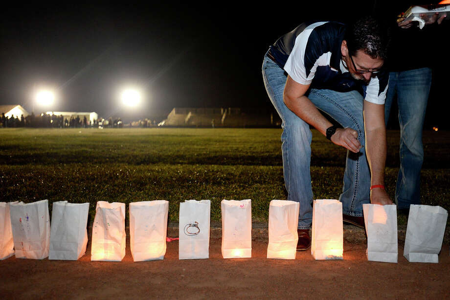"Michael Barborek lights a luminary during the ""Silsbee Strong Celebration"" on Wednesday evening. The event was held to allow the community to mourn recent tragedies, including the deaths of assistant fire chief Jay Hinkie, cheerleader Tristan Dilley and Ashley Pickering and her children. Photo taken Wednesday 11/29/17 Ryan Pelham/The Enterprise Photo: Ryan Pelham / ©2017 The Beaumont Enterprise/Ryan Pelham"