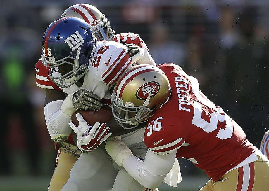 New York Giants running back Orleans Darkwa (26) is tackled by San Francisco 49ers linebacker Reuben Foster (56) and outside linebacker Eli Harold during the first half of an NFL football game in Santa Clara, Calif., Sunday, Nov. 12, 2017. (AP Photo/Ben Margot) Photo: Ben Margot, Associated Press