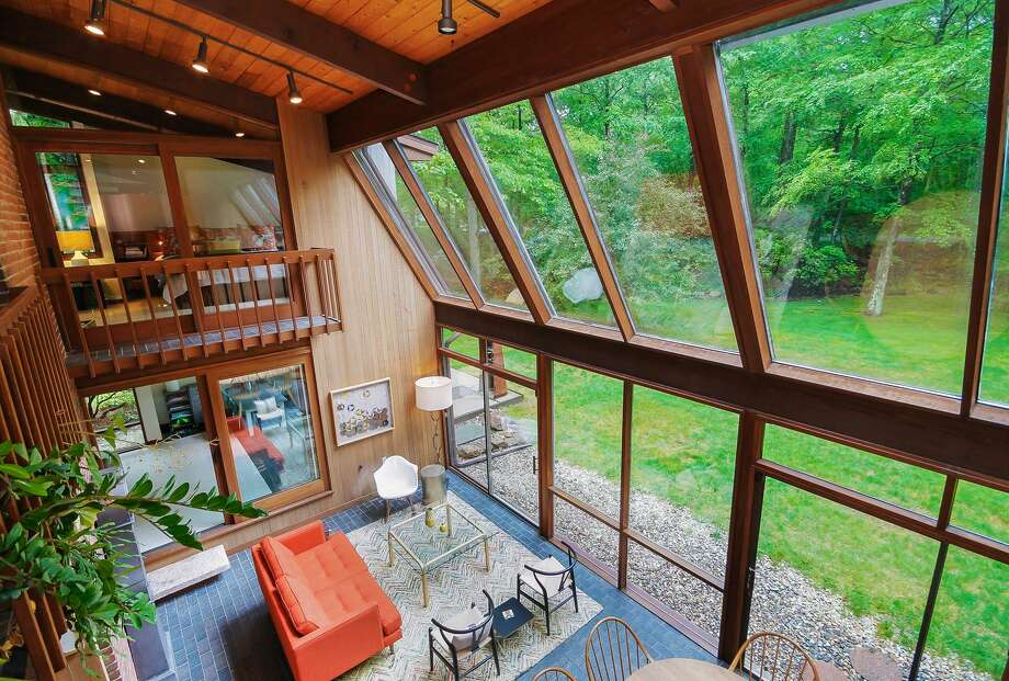 The mid-century home at 124 Armand Road in Ridgefield used to be a model home for the Deck Home company the early 1980s. The house has unique angles and mixes large windows, wood and stone to help bring nature inside. Photo: PlanOmatic / © 2017 PlanOmatic