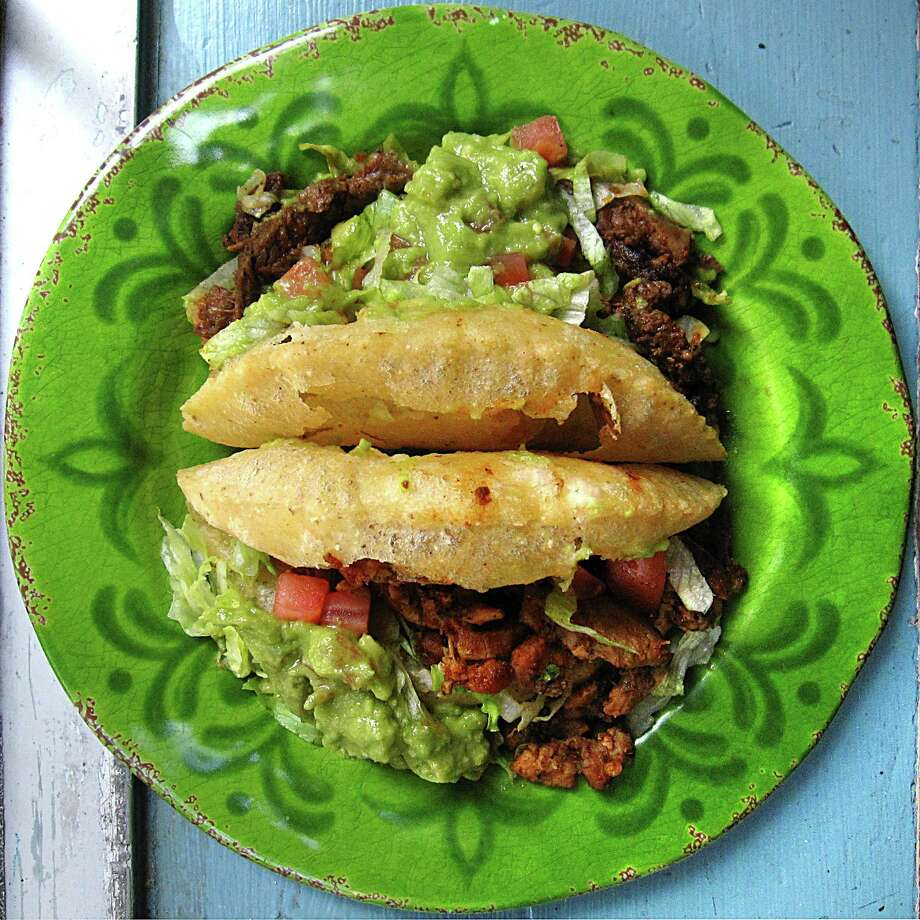 Taco of the Week: Spicy beef fajita puffy taco, top, and a spicy chicken fajita taco, both on handmade masa shells fried to order, from Henry's Puffy Tacos. Photo: Mike Sutter /San Antonio Express-News