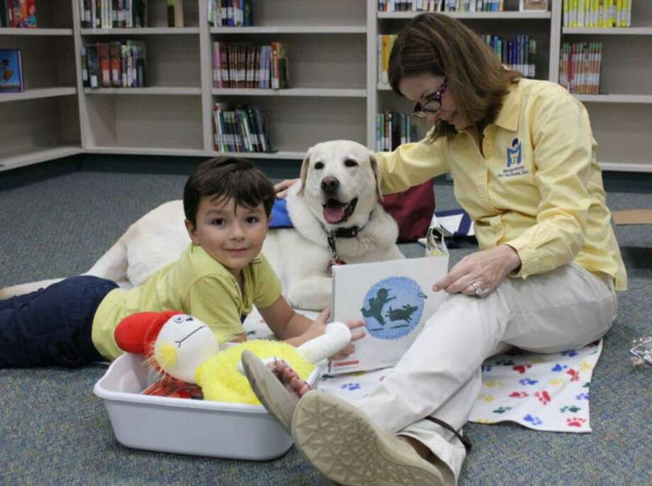 Dash and his owner listen as a child reads to them. The South Regional Library works with Montgomery Pet Partners to bring in special therapy dogs on the second Saturday of each month to provide children ages 4-12 with the opportunity to read to a non-judgmental audience. Photo: Courtesy Photo