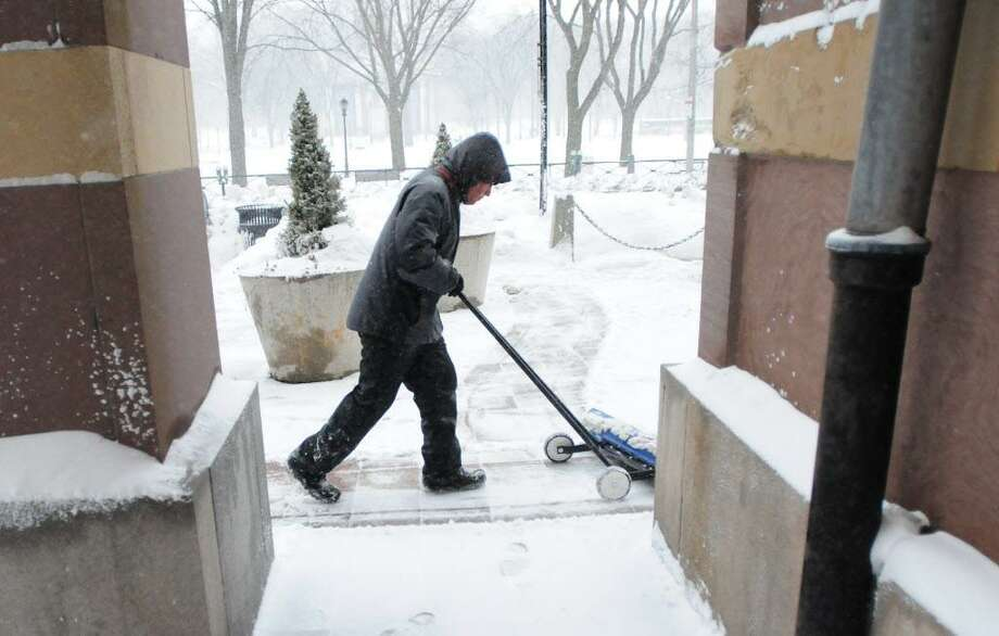 A man shovels snow on the sidewalk. Photo: File Photo / ©Peter Hvizdak /  New Haven Register