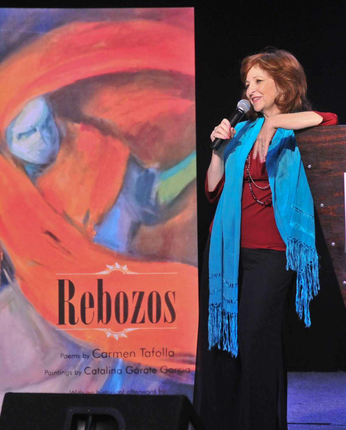 """San Antonio author and poet Laureate Carmen Tafolla spoke in front of an enlargement of her book """"Rebozos"""" during a children's book event."""