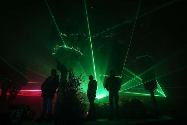 ST AUSTELL, ENGLAND - NOVEMBER 23:  People inside the Mediterranean Biome look at the lasers from the Eden Festival of Light and Sound at the Eden Project near St Austell on November 23, 2017 in Cornwall, England. A new laser light and sound show curated by renowned light artist Chris Levine, featuring original soundscapes, will be the highlight of the Eden Project's Christmas celebrations and will be open to the public from November 25 to December 30. Visitors to home of the world-famous Biomes in Cornwall, standing on the viewing platform will be able to watch lasers pierce through the darkness to create a canopy of light, painting the Biomes outside and the plant displays inside, with festive colours, whilst inside the Mediterranean Biome there will be the stage for a choreographed performance of after dark music and light.  (Photo by Matt Cardy/Getty Images)