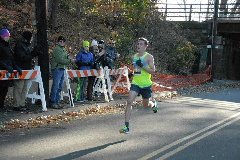 Henry Wynne of Westport runs as spectators look on during the Pequot Thanksgiving Race. Wynne won the race with a time of 24:50. Photo: Contributed Photo