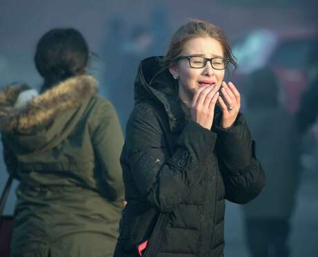 A woman is in tears as firefighters from around the region work their best to knock down a multi-alarm fire consumes a number of building on Remsen Street Thursday Nov. 30, 2017 in Cohoes, NY.  (Skip Dickstein/ Times Union) Photo: SKIP DICKSTEIN, Albany Times Union