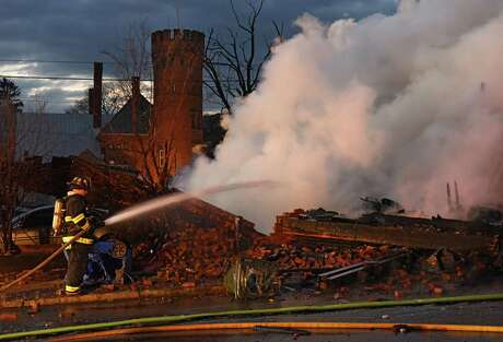 With the castle-like historic former home to Cramer's Armory building still standing in the background, firefighters douse flames. (Lori Van Buren / Times Union) / 20042290A