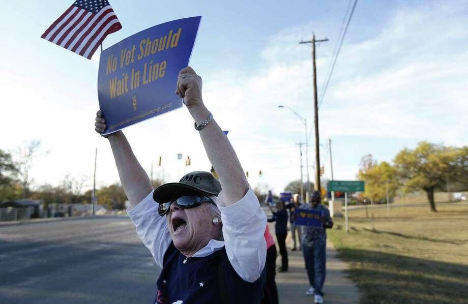 Karen Dueweke of Kerrville holds a sign and an American flag at a rally by members of the American Federation of Government Employees outside the VA hospital in Kerrville to demand the agency fill 49,000 vacancies at facilities nationwide on Wednesday, Nov. 29, 2017. Dueweke said her husband - a Vietnam veteran and Marine suffers from health issues from Agent Orange. She is frustrated by the long wait times that are required for appointments when medical issues arise. She doesn't fault the VA staff and wishes the staffing issues would be addressed. The rally is one of more than 50 held since June across the country and the only one planned near San Antonio at this point. Veterans and family members of veterans also joined in the rally to demand improved medical services for all veterans. (Kin Man Hui/San Antonio Express-News) Photo: Kin Man Hui, Staff / San Antonio Express-News / ©2017 San Antonio Express-News