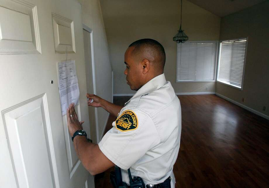 Contra Costa County Sheriff's Deputy Doug Odom posts an eviction notice at an Antioch home in 2008, during a recession that cost millions their homes. Photo: Paul Chinn, SFC