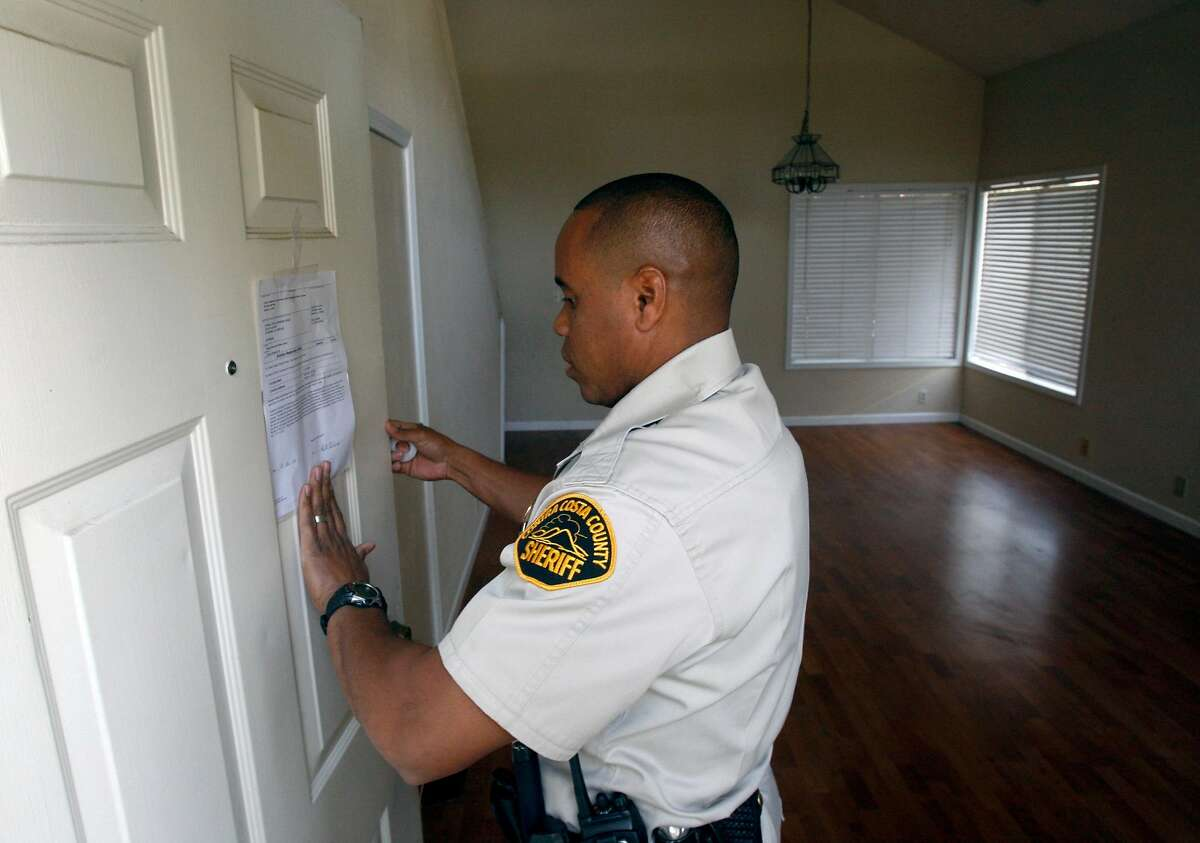 Contra Costa County Sheriff's deputy Doug Odom posts an eviction notice on a home in Antioch, Calif., on Tuesday, Feb. 26, 2008. The tenants had already moved out when the deputies arrived. Photo by Paul Chinn / San Francisco Chronicle