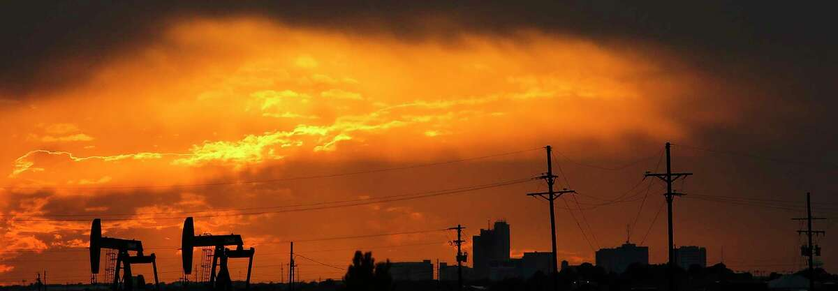 The sun sets behind the Midland skyline as pumpjacks work outside the city limits Thursday, Sept. 15, 2016. ( Michael Ciaglo / Houston Chronicle )