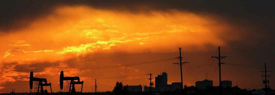 The sun sets behind the Midland skyline as pumpjacks work outside the city limits Thursday, Sept. 15, 2016. ( Michael Ciaglo / Houston Chronicle ) Photo: Michael Ciaglo, Staff / © 2016  Houston Chronicle