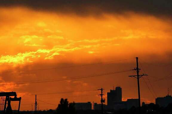 The sun sets behind the Midland skyline as pumpjacks work outside the city limits Thursday, Sept. 15, 2016. ( Michael Ciaglo / Houston Chronicle )