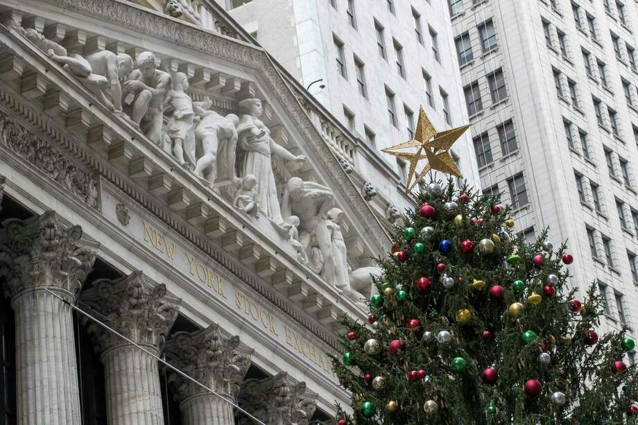 A golden star tops the Christmas tree outside the New York Stock Exchange, Thursday, Nov. 30, 2017. Stocks powered to new highs on Wall Street, giving the Dow Jones industrials their biggest gain since March and putting them past 24,000 for the first time. (AP Photo/Mary Altaffer) ORG XMIT: NYMA102 Photo: Mary Altaffer / Copyright 2017 The Associated Press. All rights reserved.