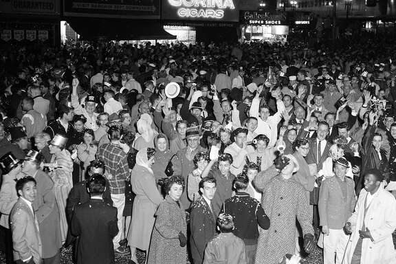 The happy crowds waits for midnight at New Year's Eve celebrations on Market Street in San Francisco, December 31, 1959