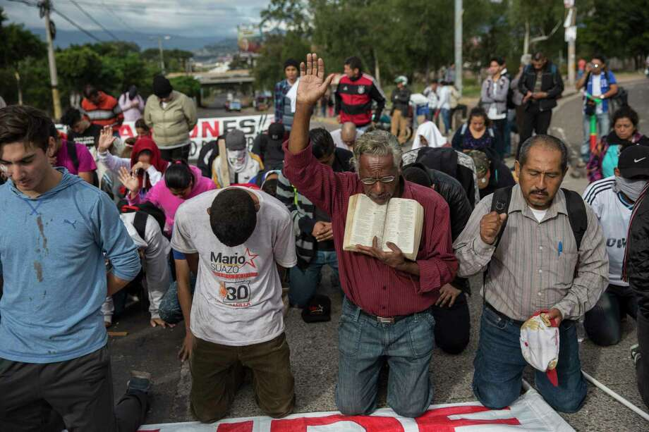 Supporters of Libre Alliance presidential candidate Salvador Nasralla kneel in prayer during a protest outside the National Institute of Professional Training, where election ballots are stored, in Tegucigalpa, Honduras, Thursday, Nov. 30, 2017. Nasralla has alleged fraud and said he won't respect the official results. He's watched an initial five-point lead diminish in recent days as official results have trickled out, giving incumbent President Juan Orlando Hernandez a slim lead for re-election. (AP Photo/Rodrigo Abd) Photo: Rodrigo Abd, STF / Copyright 2017 The Associated Press. All rights reserved.