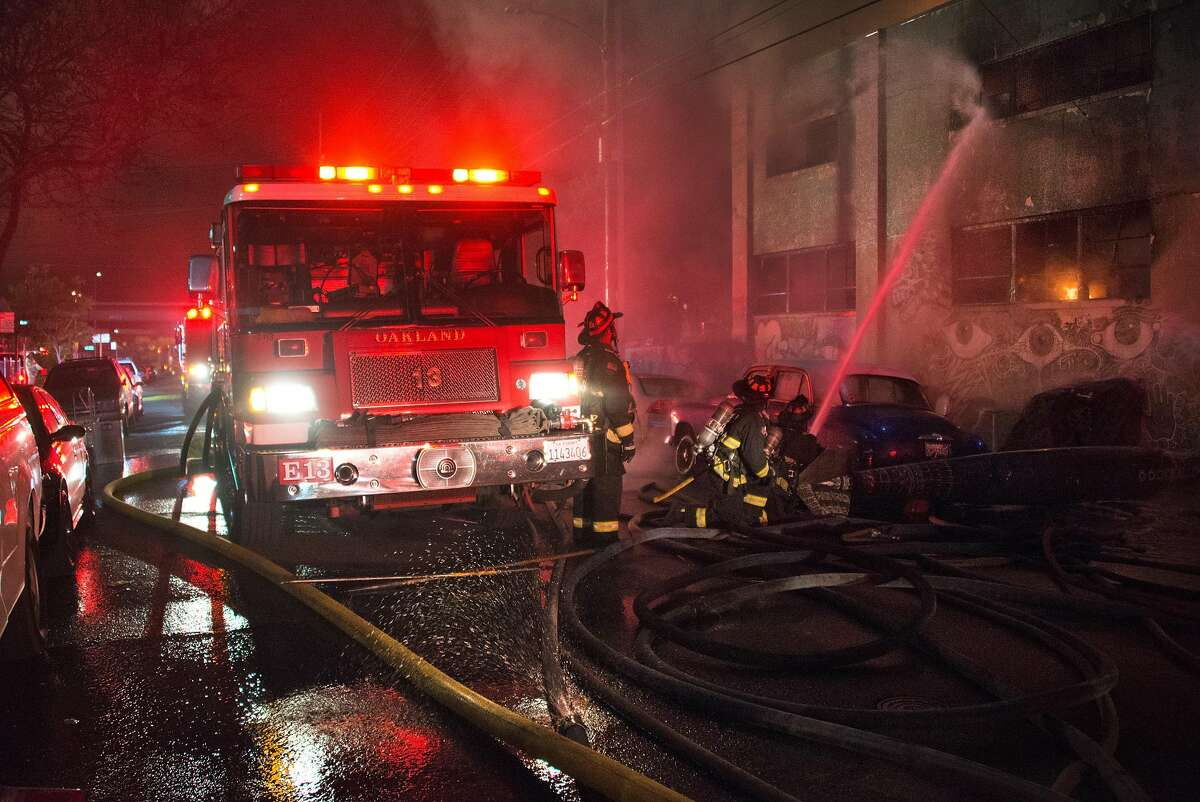 Firefighters work at the scene on 31st Avenue in Oakland on Dec. 3, 2016.