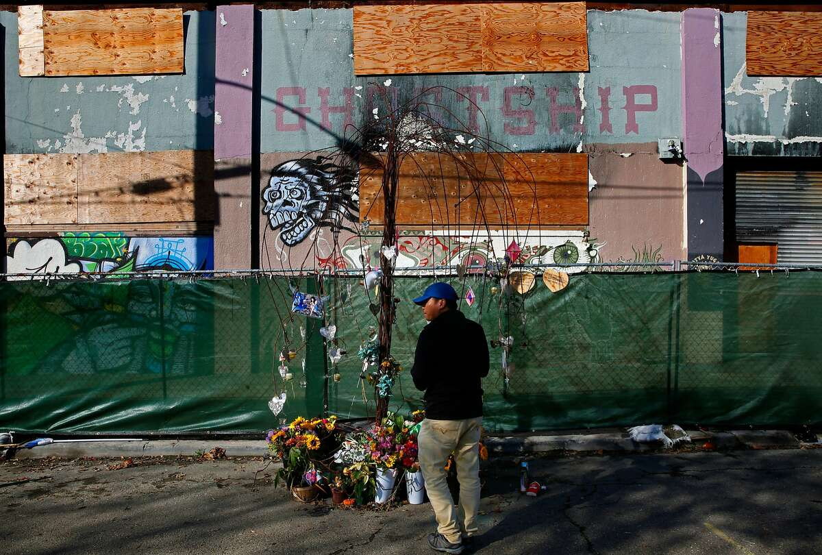 David Nguyen of El Cerrito stopped to look a memorial to the victims of the Ghost Ship warehouse fire that killed 36 people last December 2nd, as seen on Tuesday Nov. 28, 2017, in Oakland, Calif.