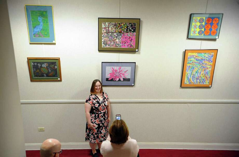 "Meghan McCormack poses for a photo by her artwork during The Kennedy Center's. 2018 ""A Unique Perspective"" Calendar reception held at the Margaret E. Morton Government Center in Bridgeport, Conn., Nov. 30, 2017. Each year the calendar brings joy to the talented artists who are recognized at the annual calendar reception and brightens the season with its vibrant artwork. Photo: Christian Abraham / Hearst Connecticut Media / Connecticut Post"