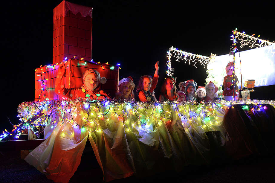 Parade participants wave to the crowd and toss candy from their festive holiday floats during the annual Lumberton Lighted Christmas Parade Thursday. Photo taken Thursday, November 30, 2017 Kim Brent/The Enterprise Photo: Kim Brent / BEN