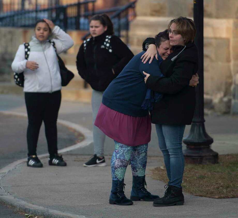 A woman is comforted by a bystander as firefighters from around the region work their best to knock down a multi-alarm fire consumes a number of building on Remsen Street Thursday Nov. 30, 2017 in Cohoes, NY.  (Skip Dickstein/ Times Union) Photo: SKIP DICKSTEIN
