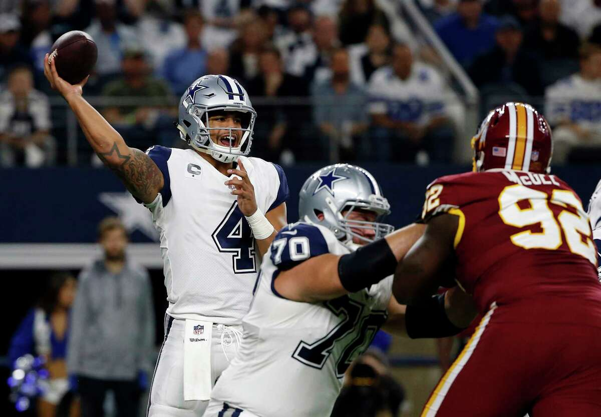 Dallas Cowboys quarterback Dak Prescott (4) throws a pass as guard Zack Martin (70) helps defend against a rush by Washington Redskins defensive tackle Stacy McGee (92) in the first half of an NFL football game, Thursday, Nov. 30, 2017, in Arlington, Texas. (AP Photo/Ron Jenkins) ORG XMIT: CBS106
