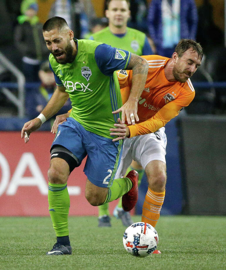 Seattle Sounders midfielder Clint Dempsey (2) tries to free himself from the grasp of Houston Dynamo midfielder Eric Alexander, right, during the first half of the second leg of the MLS soccer Western Conference final, Thursday, Nov. 30, 2017, in Seattle. Alexander was shown a yellow card on the play. (AP Photo/Ted S. Warren) Photo: Ted S. Warren/Associated Press