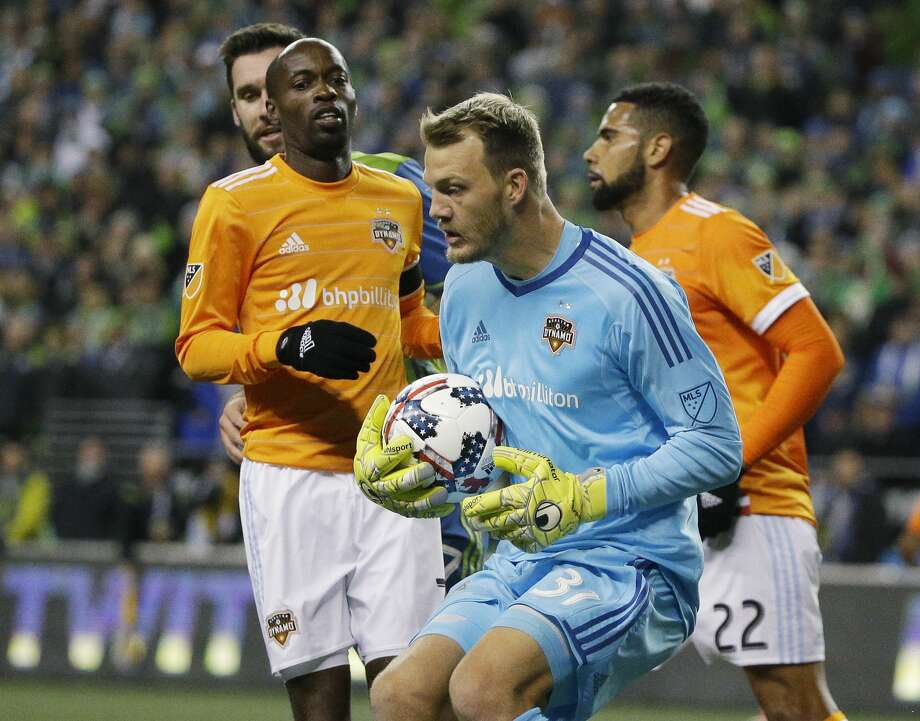 Houston Dynamo goalkeeper Joe Willis, center, hold the ball as midfielder DaMarcus Beasley, left, and defender Leonardo (22) watch during the first half of the second leg of the MLS soccer Western Conference final against the Seattle Sounders, Thursday, Nov. 30, 2017, in Seattle. (AP Photo/Ted S. Warren) Photo: Ted S. Warren/Associated Press