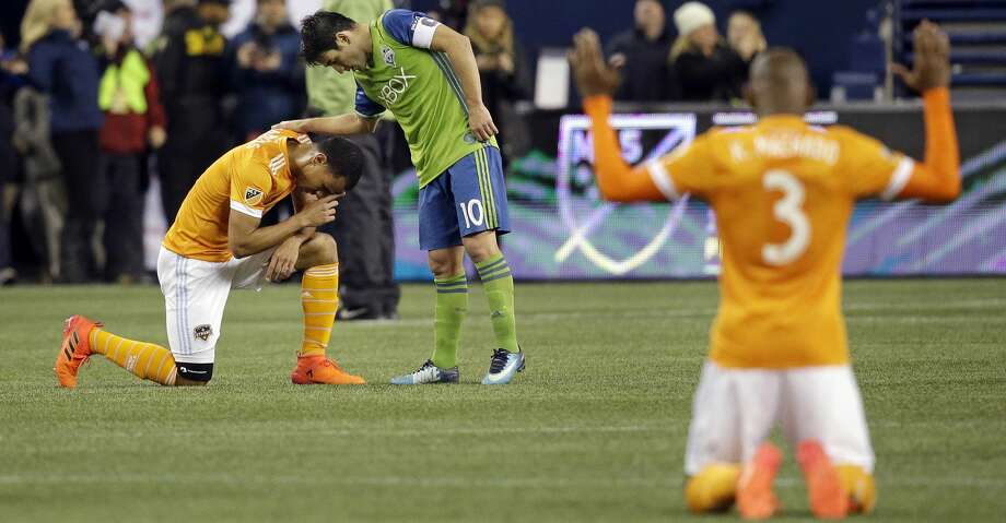 Seattle Sounders' Nicolas Lodeiro (10) leans over to greet Houston Dynamo's Juan David Cabezas as Adolfo Machado (3) kneels in surrender nearby after the Sounders defeated the Dynamo 3-0 in the second leg of the MLS soccer Western Conference final, Thursday, Nov. 30, 2017, in Seattle. The Sounders advanced to the MLS Cup. (AP Photo/Elaine Thompson) Photo: Elaine Thompson/Associated Press