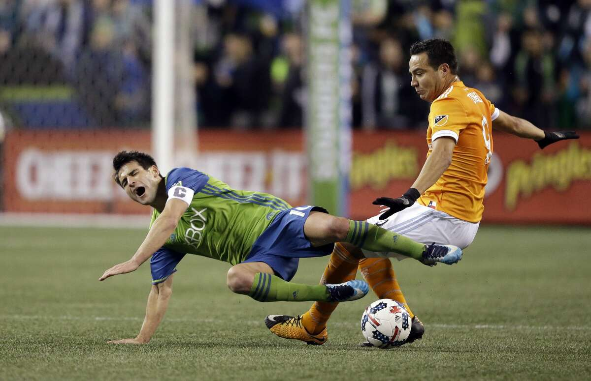 Seattle Sounders' Nicolas Lodeiro, left, is tripped by Houston Dynamo's Erick Torres during the second half of the second leg of the MLS soccer Western Conference final, Thursday, Nov. 30, 2017, in Seattle. (AP Photo/Elaine Thompson)