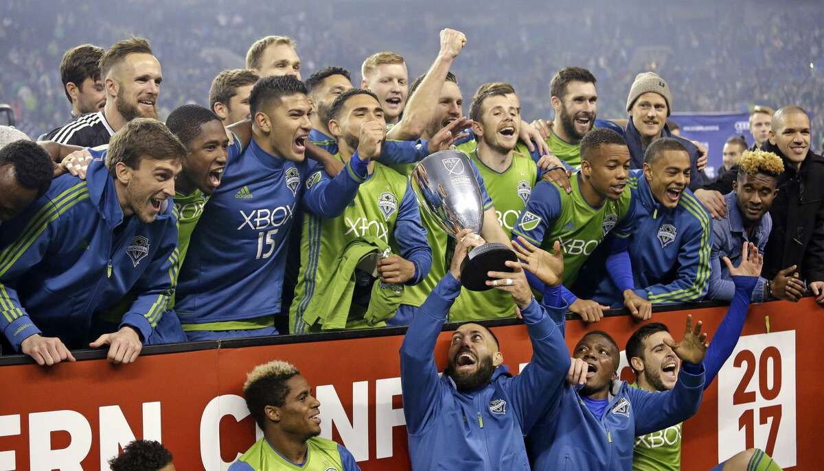 Seattle Sounders' Clint Dempsey holds the championship trophy up as teammates cheer around him after the Sounders defeated the Houston Dynamo 3-0 in the second leg of the MLS soccer Western Conference final, Thursday, Nov. 30, 2017, in Seattle. The Sounders advanced to the MLS Cup. (AP Photo/Elaine Thompson)