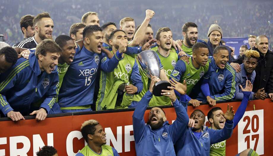 Seattle Sounders' Clint Dempsey holds the championship trophy up as teammates cheer around him after the Sounders defeated the Houston Dynamo 3-0 in the second leg of the MLS soccer Western Conference final, Thursday, Nov. 30, 2017, in Seattle. The Sounders advanced to the MLS Cup. (AP Photo/Elaine Thompson) Photo: Elaine Thompson/Associated Press