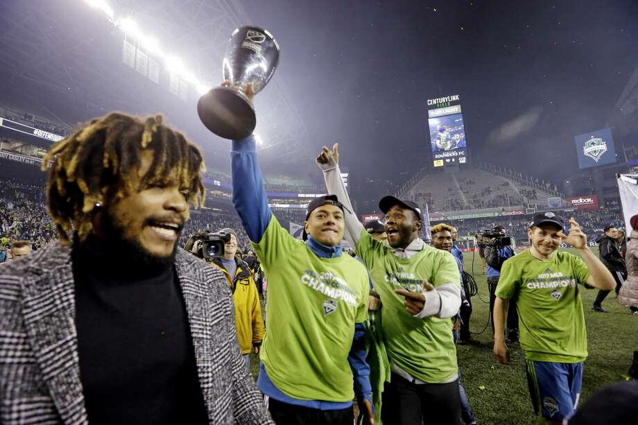 Seattle Sounders players cheer as one holds the conference trophy after the Sounders defeated the Houston Dynamo 3-0 in the second leg of the MLS soccer Western Conference final, Thursday, Nov. 30, 2017, in Seattle. The Sounders won an aggregate and advanced to the MLS Cup. (AP Photo/Elaine Thompson) Photo: Elaine Thompson/Associated Press
