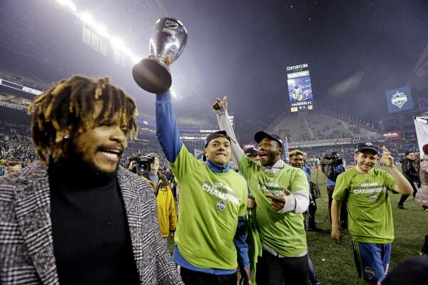 Seattle Sounders players cheer as one holds the conference trophy after the Sounders defeated the Houston Dynamo 3-0 in the second leg of the MLS soccer Western Conference final, Thursday, Nov. 30, 2017, in Seattle. The Sounders won an aggregate and advanced to the MLS Cup. (AP Photo/Elaine Thompson)