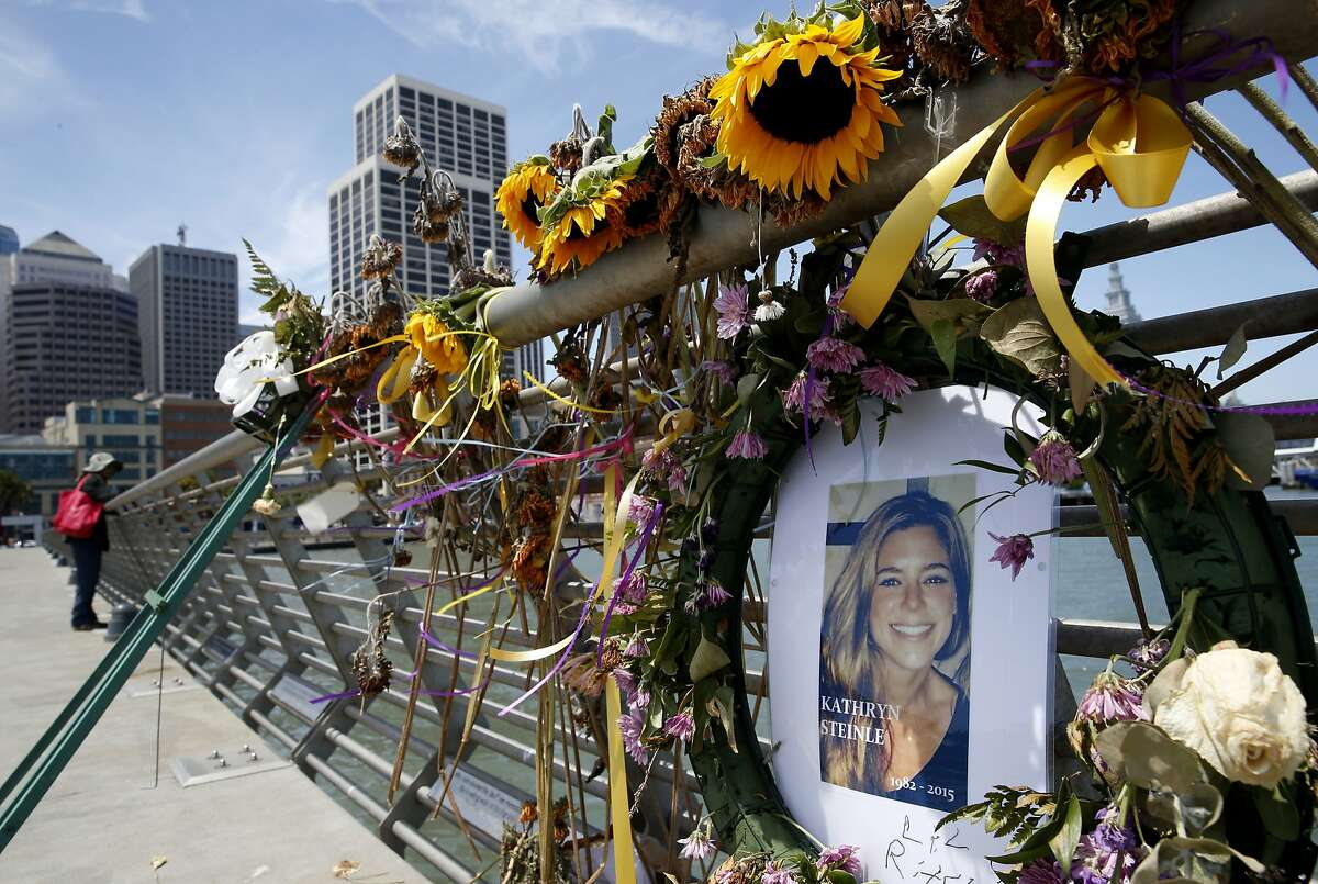 FILE - In this July 17, 2015 file photo, flowers and a portrait of Kate Steinle remain at a memorial site on Pier 14 in San Francisco. A jury has reached a verdict Thursday, Nov. 30, 2017, in the trial of Mexican man at center of immigration debate in the San Francisco pier shooting. (Paul Chinn/San Francisco Chronicle via AP, File)