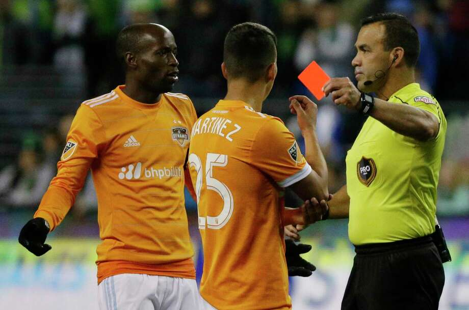 Houston Dynamo midfielder Tomas Martinez (25) is shown a red card by referee Hilario Grjeda, right, for violent conduct as midfielder DaMarcus Beasley, left, protests, in the second half of the second leg of the MLS soccer Western Conference final against the Seattle Sounders, Thursday, Nov. 30, 2017, in Seattle. The Sounders won 3-0 Thursday, giving them a 5-0 aggregate win in the two-leg series. (AP Photo/Ted S. Warren) Photo: Ted S. Warren, Associated Press / Copyright 2017 The Associated Press. All rights reserved.