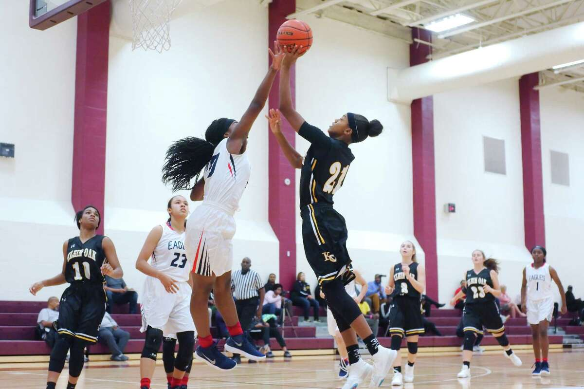 Klein Oak's Ashlyn Jones (21) tries to put up a shot over Atascocita's Shaniya Klauser (20) during the Peggy Whitley Classic basketball tournament Thursday, Nov. 30 at Clear Creek High School.