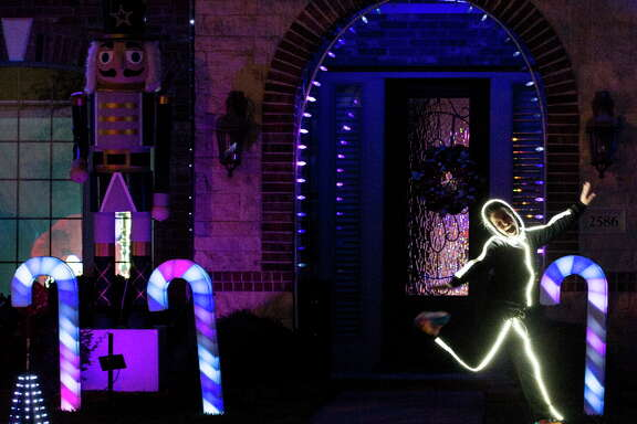 Tara Gallagher dances in front her family's home decorated to honor the Houston Astros World Series championship on Thursday, Nov. 30, 2017, in League City.