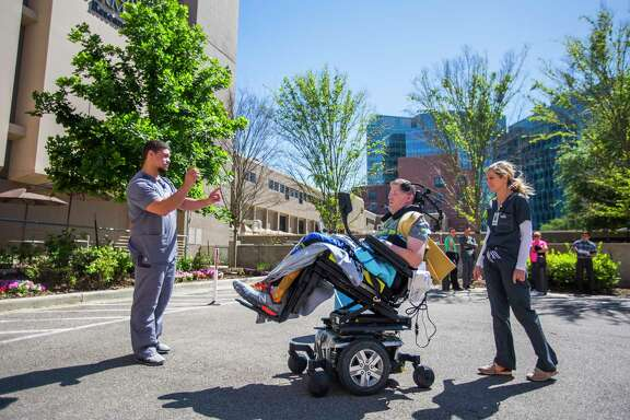 Therapists direct Nick Tullier in the use of a motorized wheelchair controlled with head movements in TIRR Memorial Hermann.