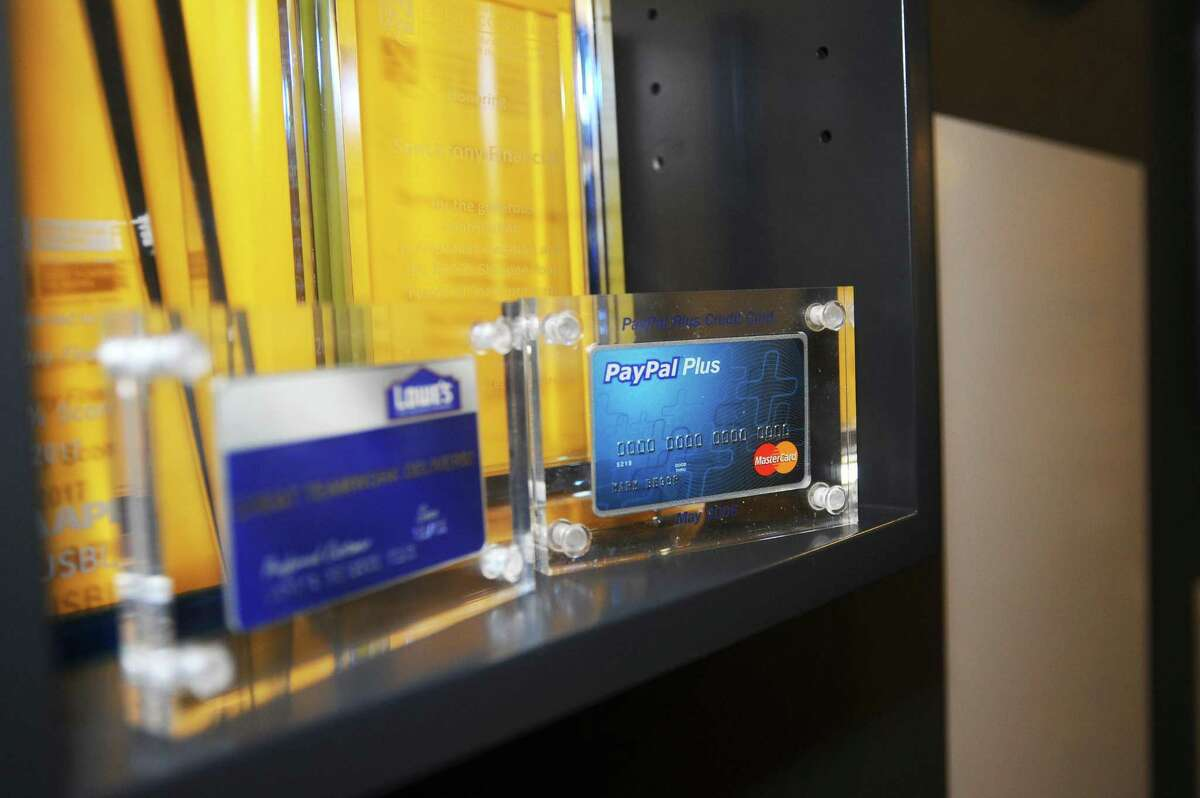 An old PayPal credit card sits encased in glass inside the Synchrony Financial headquarters at 777 Long Ridge Road in Stamford, Conn., on Monday, Nov. 27, 2017.