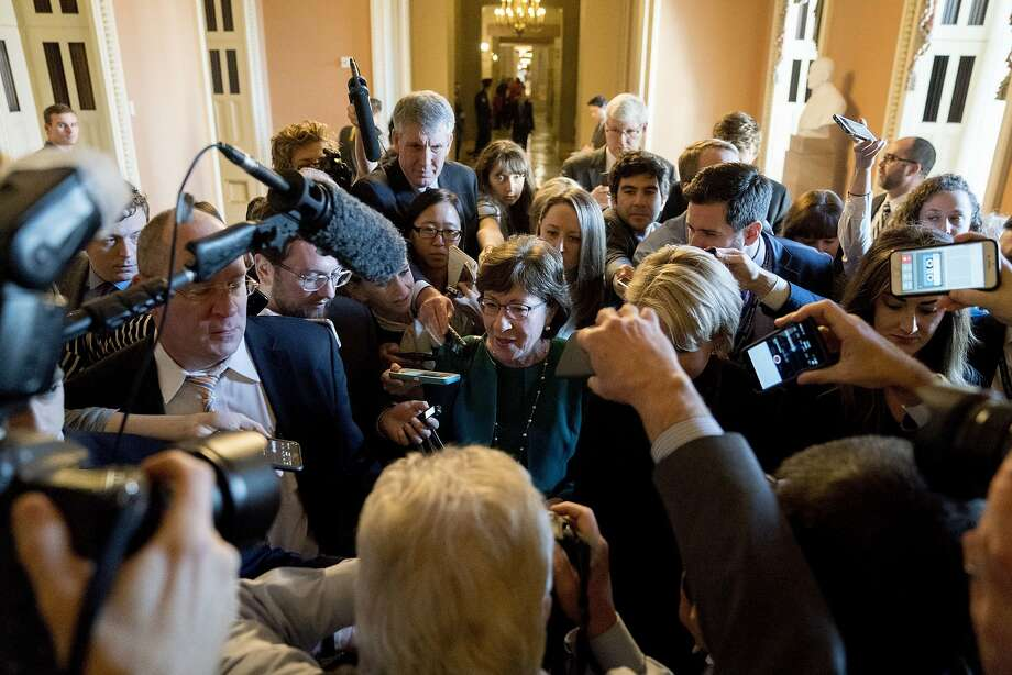 Sen. Susan Collins, R-Maine, makes her way through a crush of reporters after Republican senators met with Senate Majority Leader Mitch McConnell, R-Ky., on the GOP effort to overhaul the tax code on Capitol Hill on Friday. Photo: Andrew Harnik, Associated Press